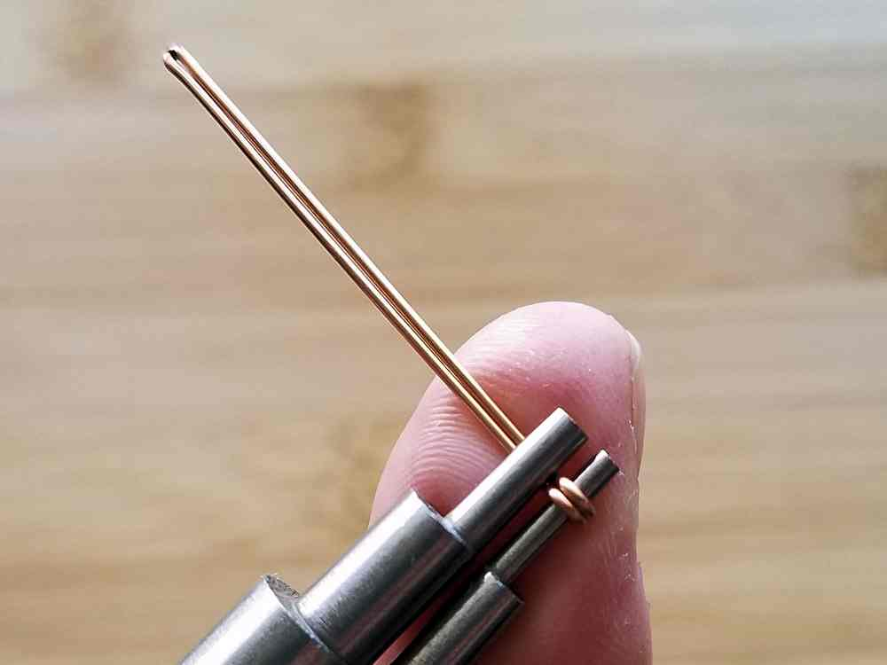 Use your thumb to tightly roll the wire around the 2mm mandrel until the cut ends of the wire touch the straight wire shafts.