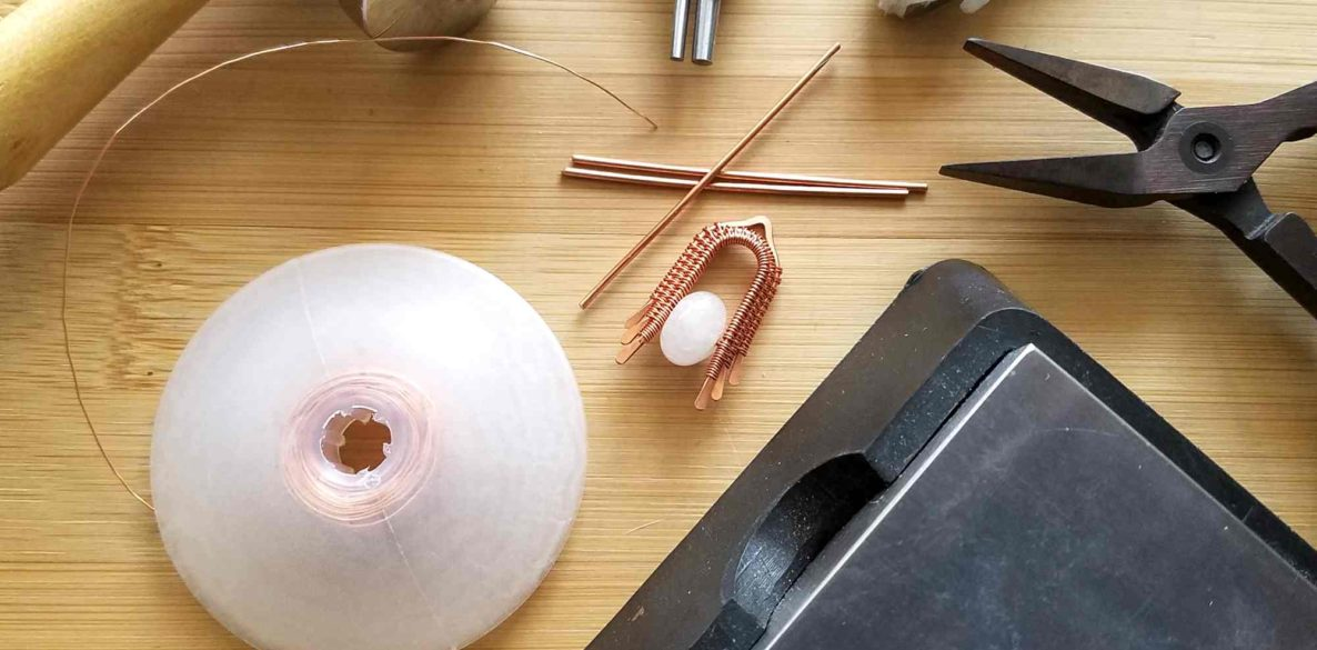 A collection of wirework tools and supplies used for wire weaving jewelry