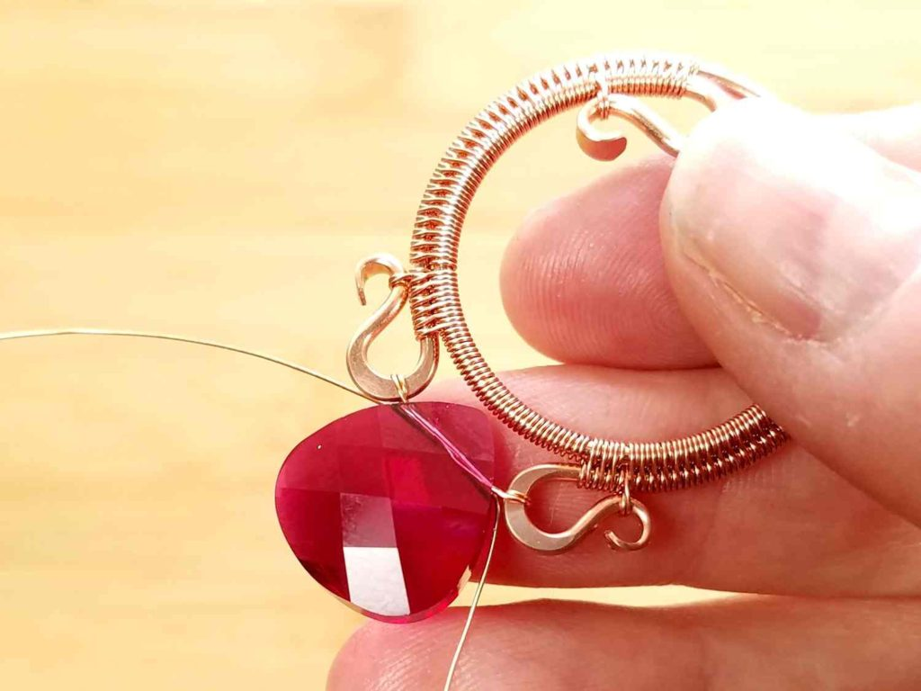 Beads Step 7 - Thread your focal bead onto the suspension wires and attach one end of the wire to the other side of Wire 2. Then thread your wire through the focal bead once more, as shown.