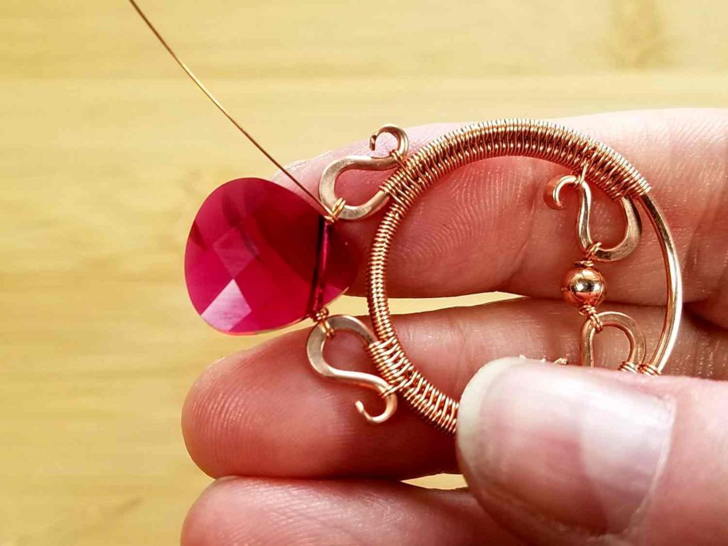 Beads Step 8 - Finish off your focal bead suspension by wrapping the wire tails securely 2 or 3 times. Break the wire tails on the back of the pendant, as shown.