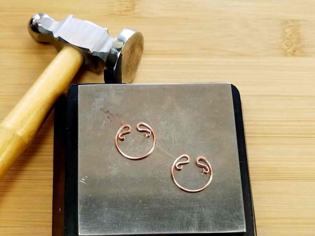 Form the Bead Frames, Step 6 - Flatten the curled ends of Wire 1 with a chasing hammer and bench block, as shown.