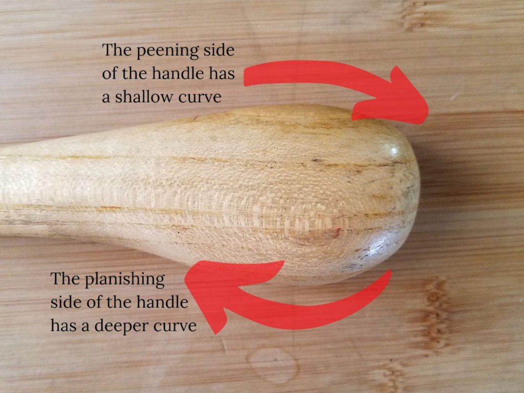 The chasing hammer handle has a distinct shape with a shallow curve on the peening side of the handle and a deeper curve on the planishing side, as shown here.