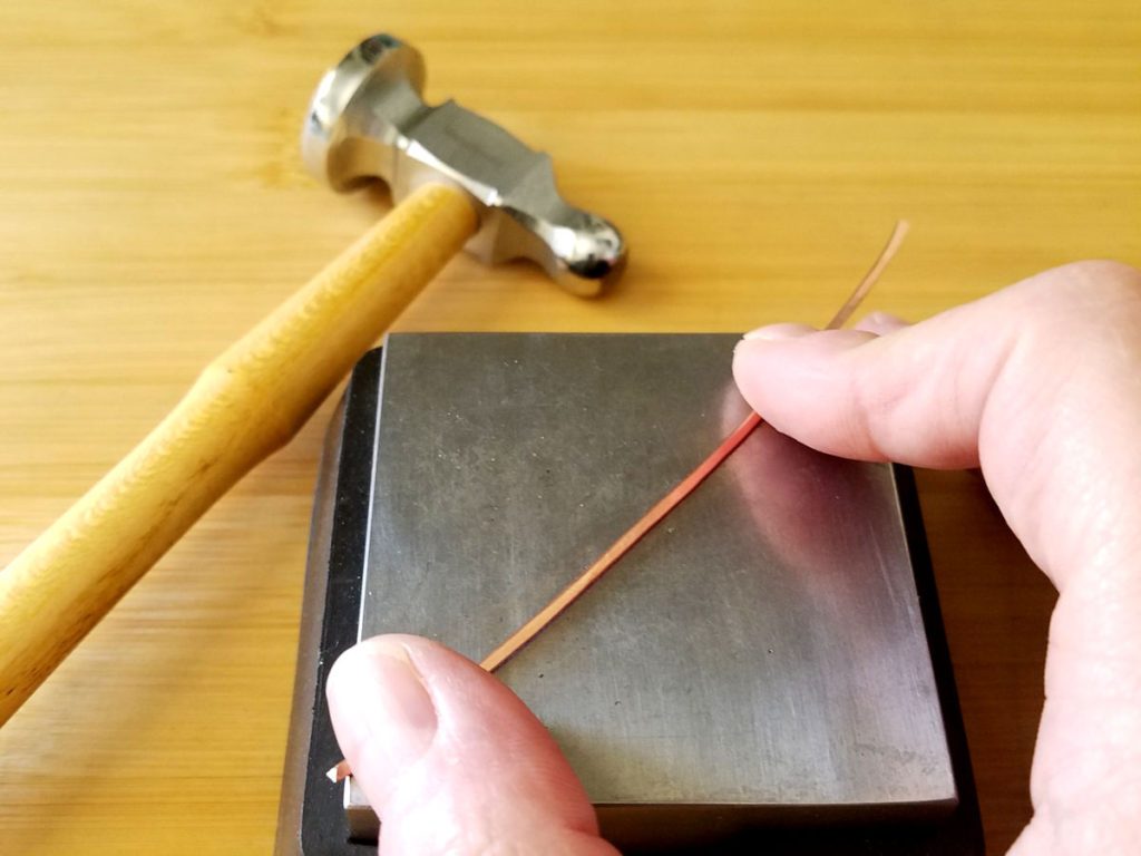 To texture wire, hold the wire steady on your bench block, as shown. Then bounce the peen evenly over the wire.