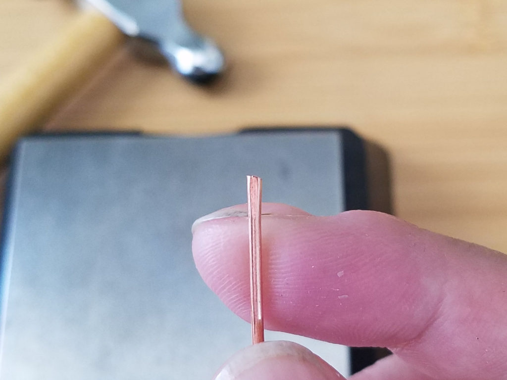 A closeup view of a piece of 16ga wire after testing hammer stroke force