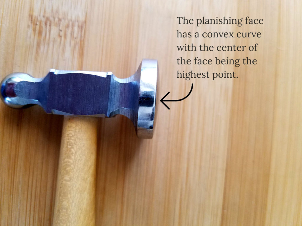 The planishing face of the chasing hammer has a slightly convex surface with the center of the face being the highest point, as shown in this image.