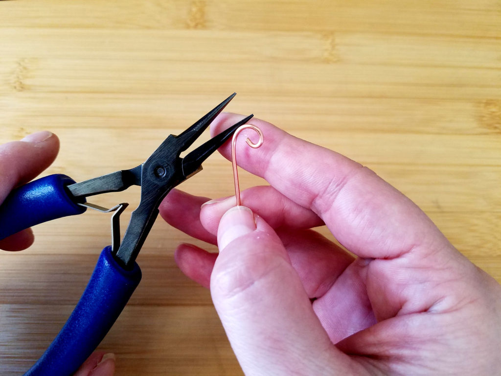 Here I made a simple curl on the end of a piece of scrap wire with my chain nose pliers. We're now going to hammer this curl to create more dimension.