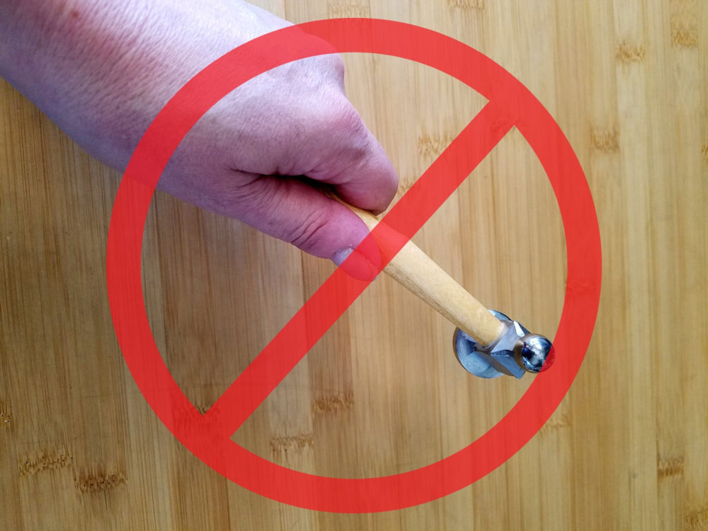 This image shows the wrong way to hold a chasing hammer. This is a common mistake that beginners tend to make.