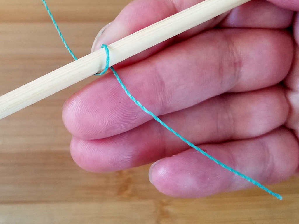 Step 2 - Wrap the weaving wire once around the first core wire, from front to back, as shown.