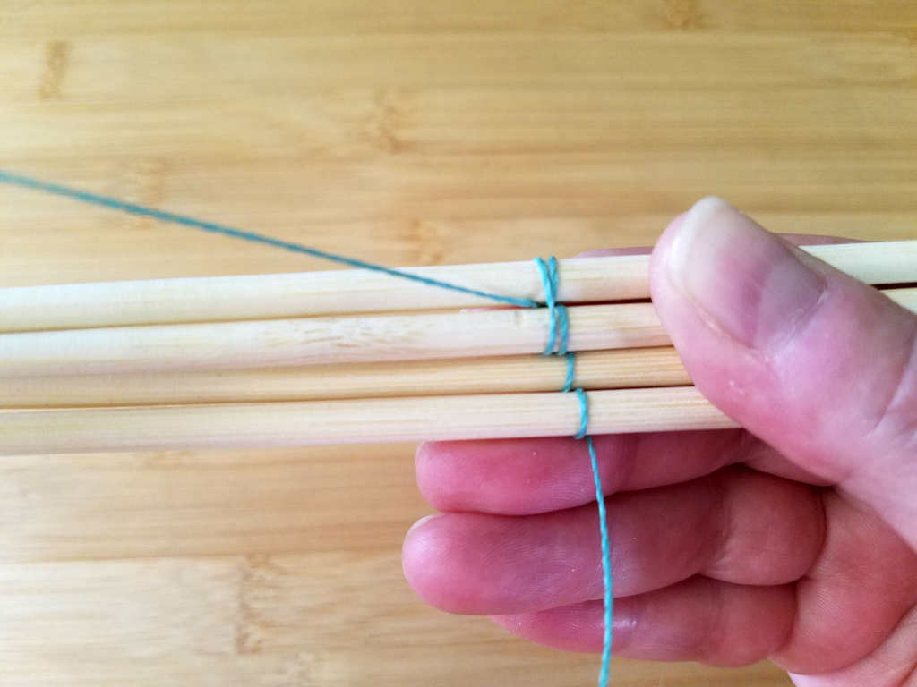 The first double wrap is completed by bringing the wire to the front between wires 3 and 4, as shown.