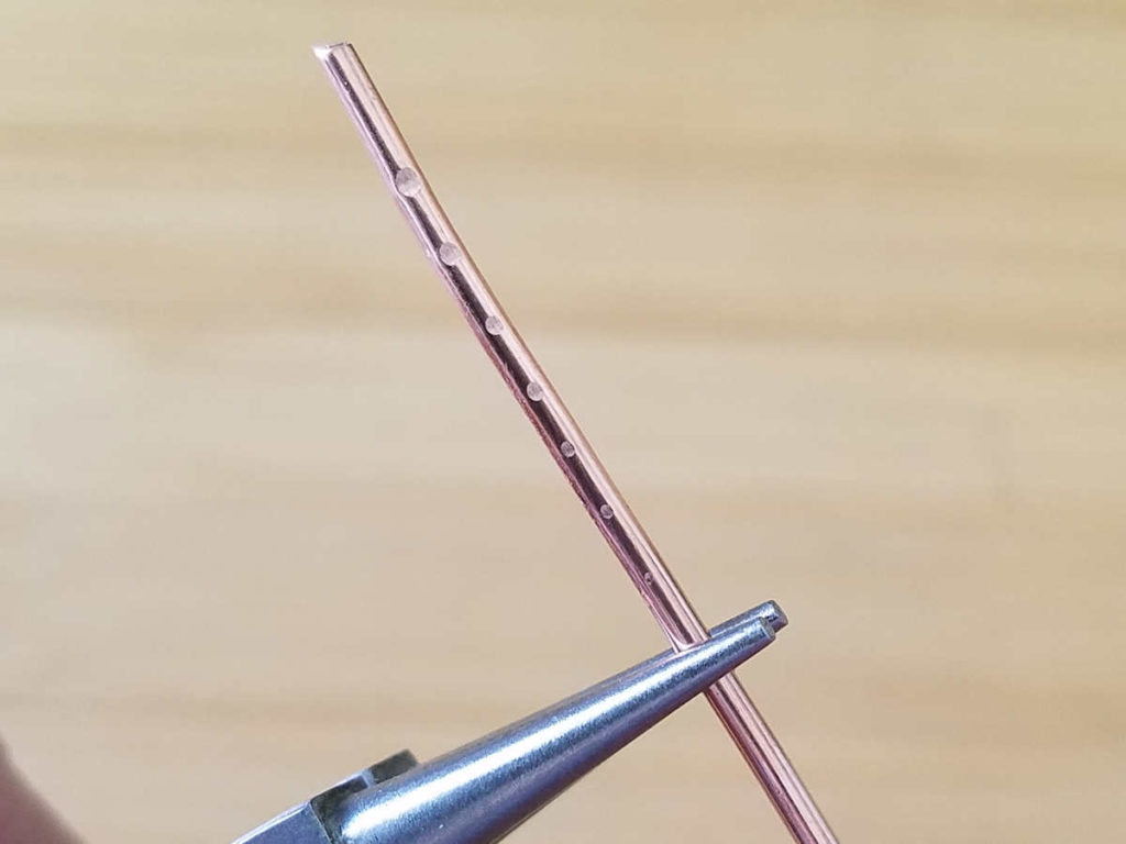 This image shows the tool marks that the author made on a piece of 14ga copper wire using incrementally lighter pressure on her grip. There are seven tool marks fading from the large tool mark created with the first test to a barely visible mark created with the lightest grip.