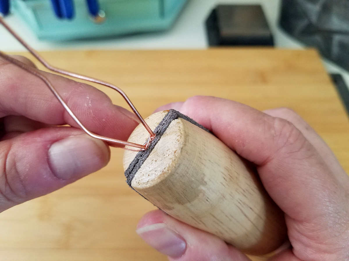 In this image, the author is using a ring clamp to protect the woven portion of the bail while continuing the weaving process.