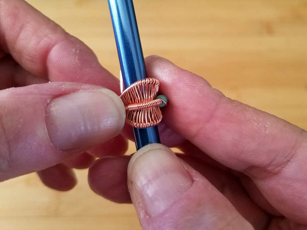 In this image, the author has coiled the weaving wire around the beaded core wire and is now continuing to lay the beaded wire around the backside of the bail.