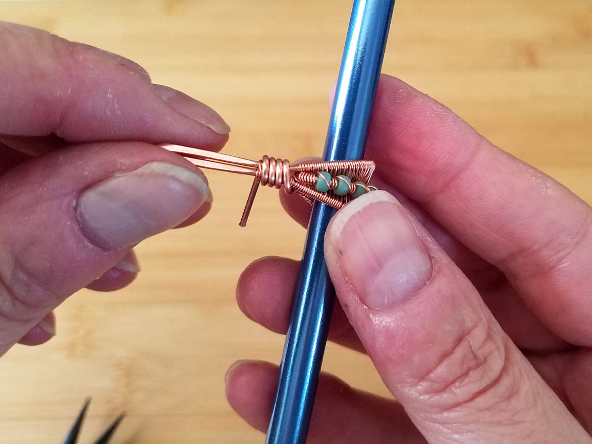 In this image, the author is coiling the remaining core wire around the folded point of the bail and the central core wire. This coil will secure the beaded core in position.