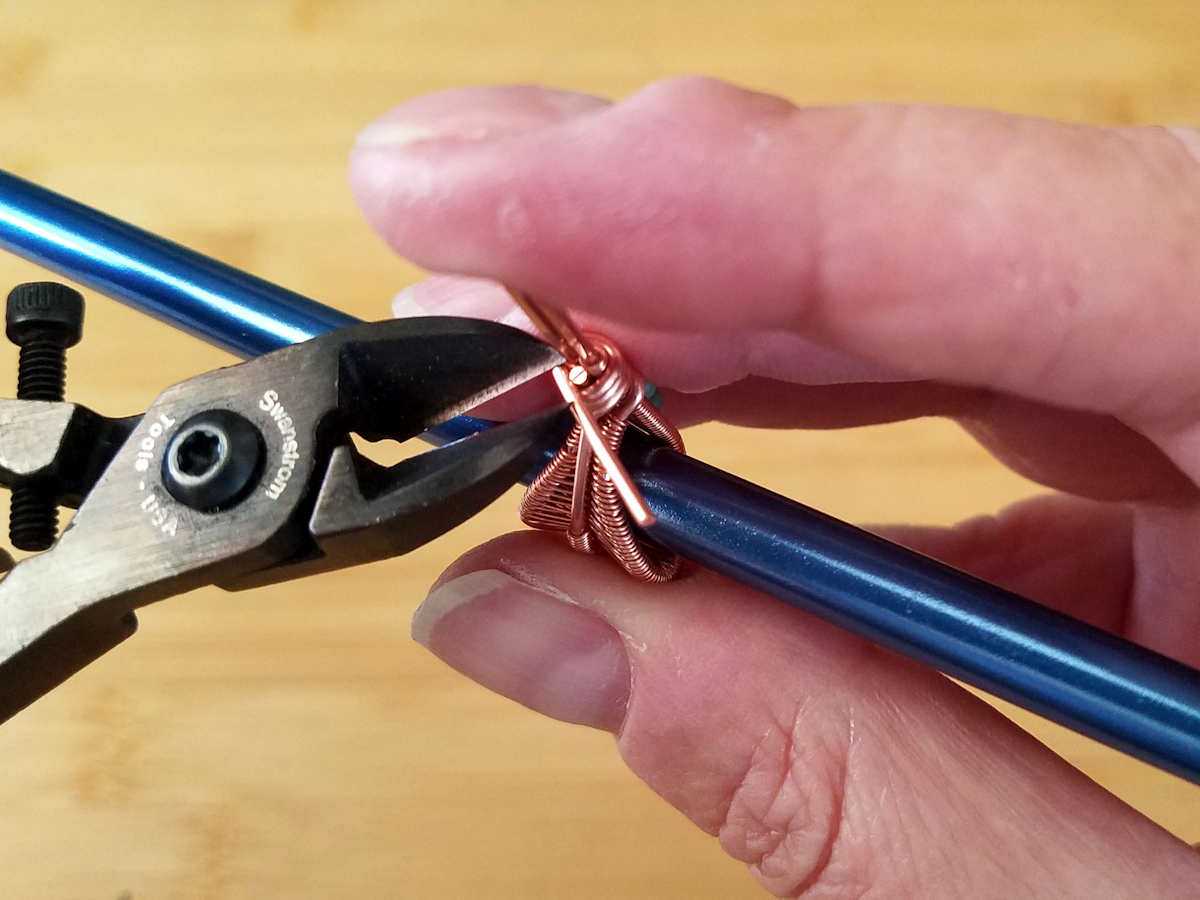 Here the author is trimming the beaded core wire flush with the coiled wire.