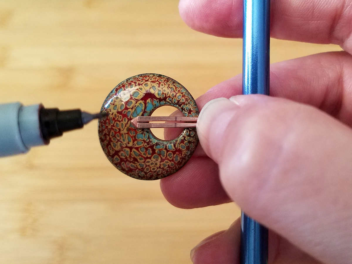 This image shows the author measuring the position of the hook in reference to the pendant that will be suspended on the finished hook.